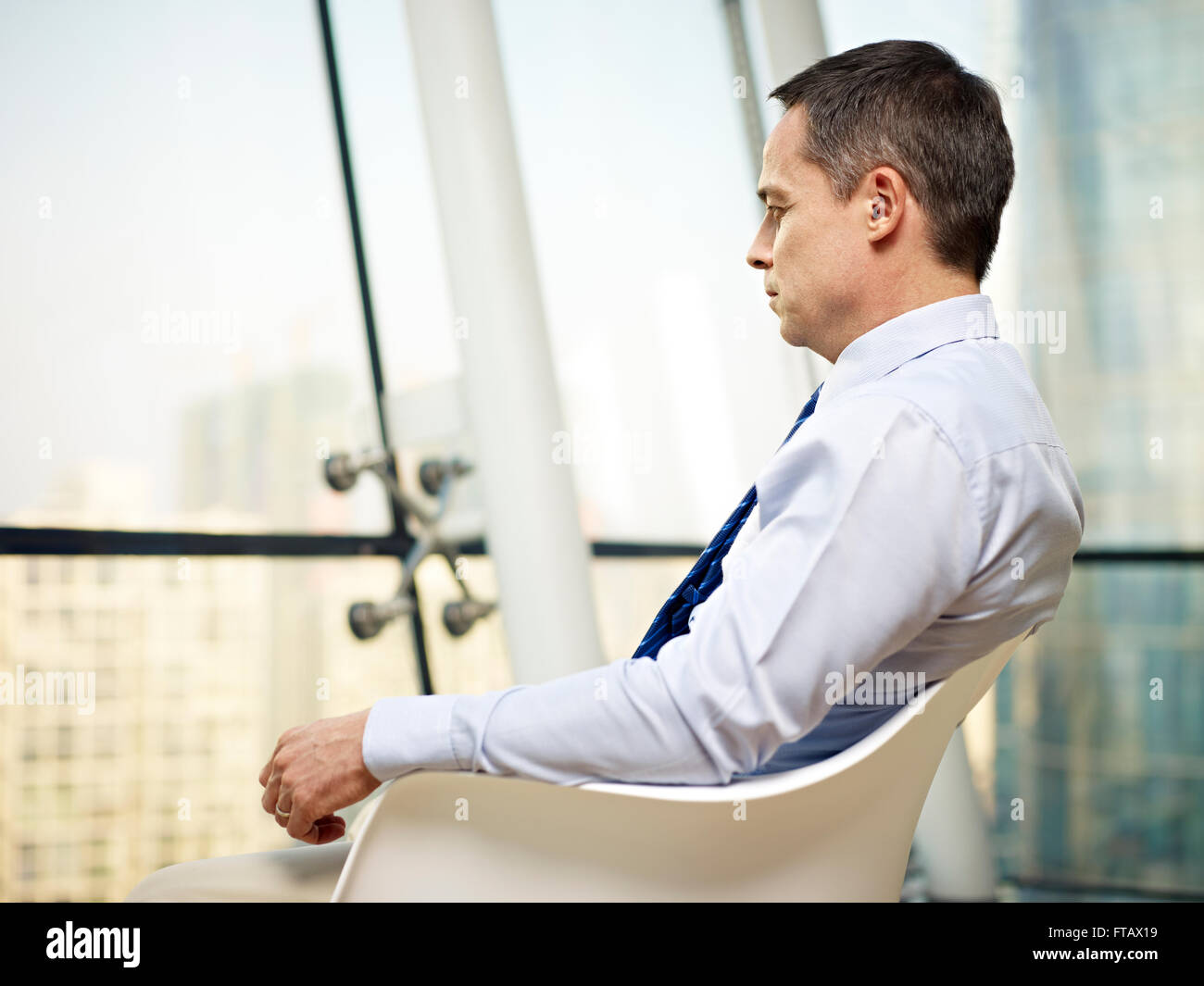 caucasian business executive sitting by the window in a chair thinking in office. - Stock Image