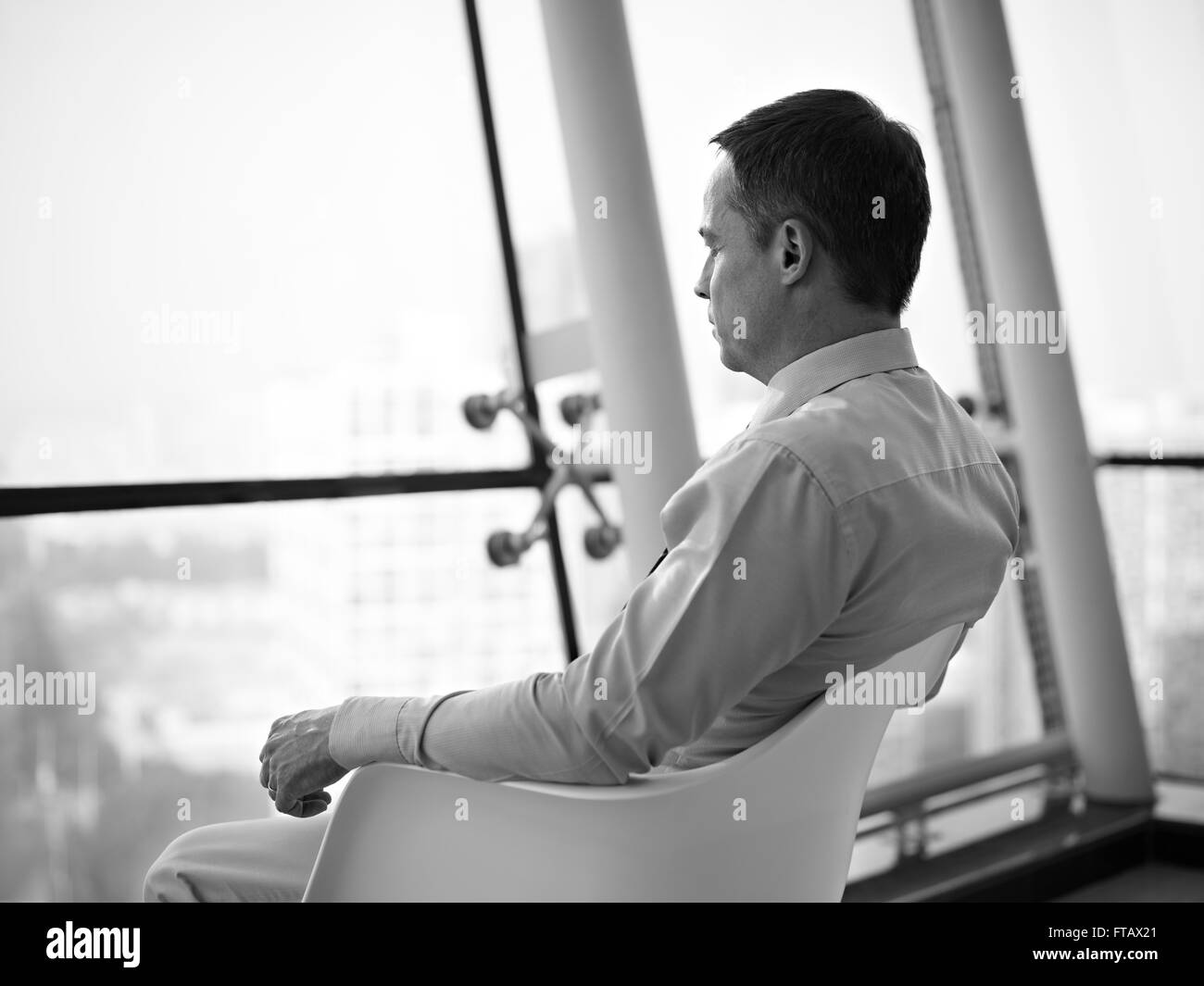 business executive sitting by the window thinking - Stock Image