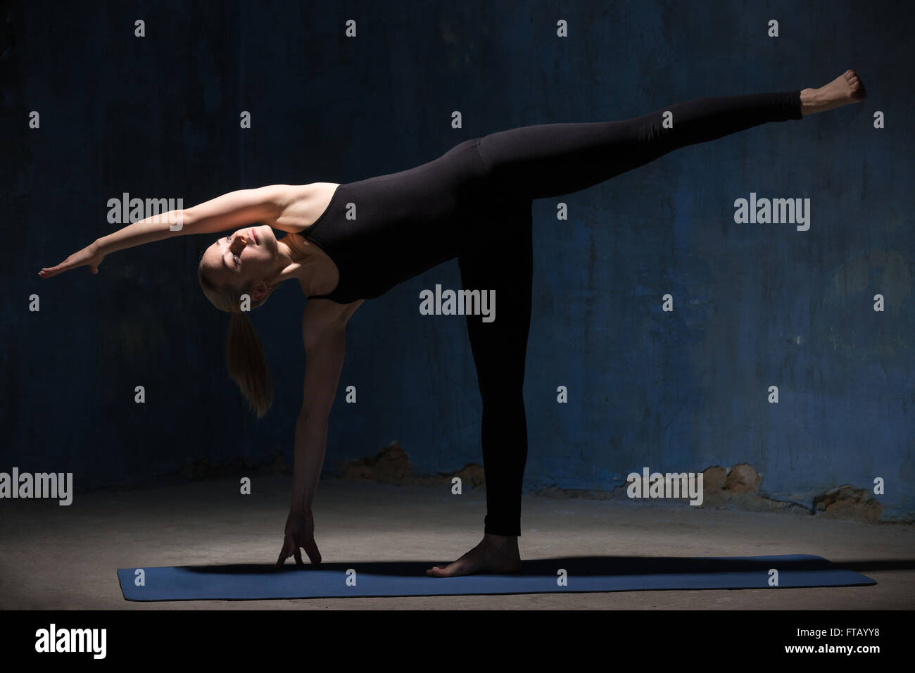 Portrait of attractive cool sporty young woman in black sportswear working out indoors against grunge dark blue - Stock Image