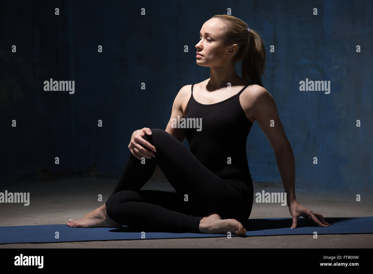 Portrait of beautiful sporty fit young woman in black sportswear working out indoors against grunge dark blue wall - Stock Image