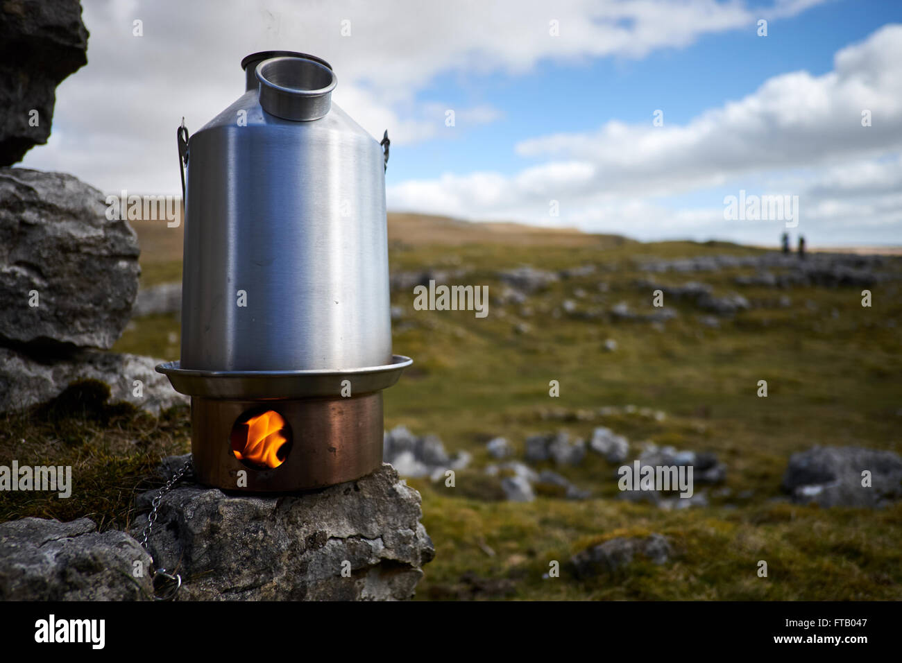 A kettle stove burning showing flames in the fire box sat on a rock with rock and grass in the background. - Stock Image