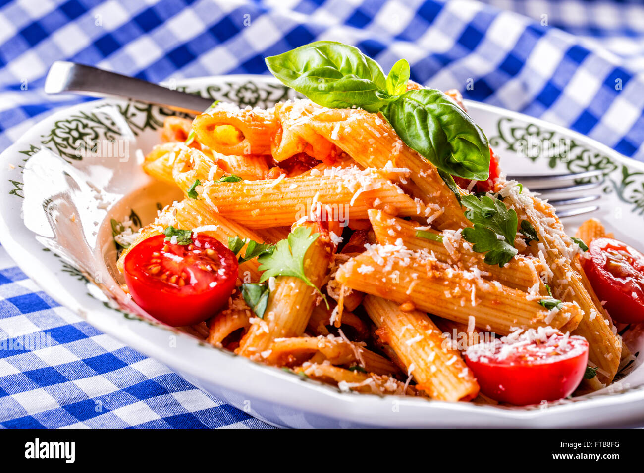Plate with pasta pene Bolognese sauce cherry tomatoes parsley top and basil leaves on checkered blue tablecloth. - Stock Image