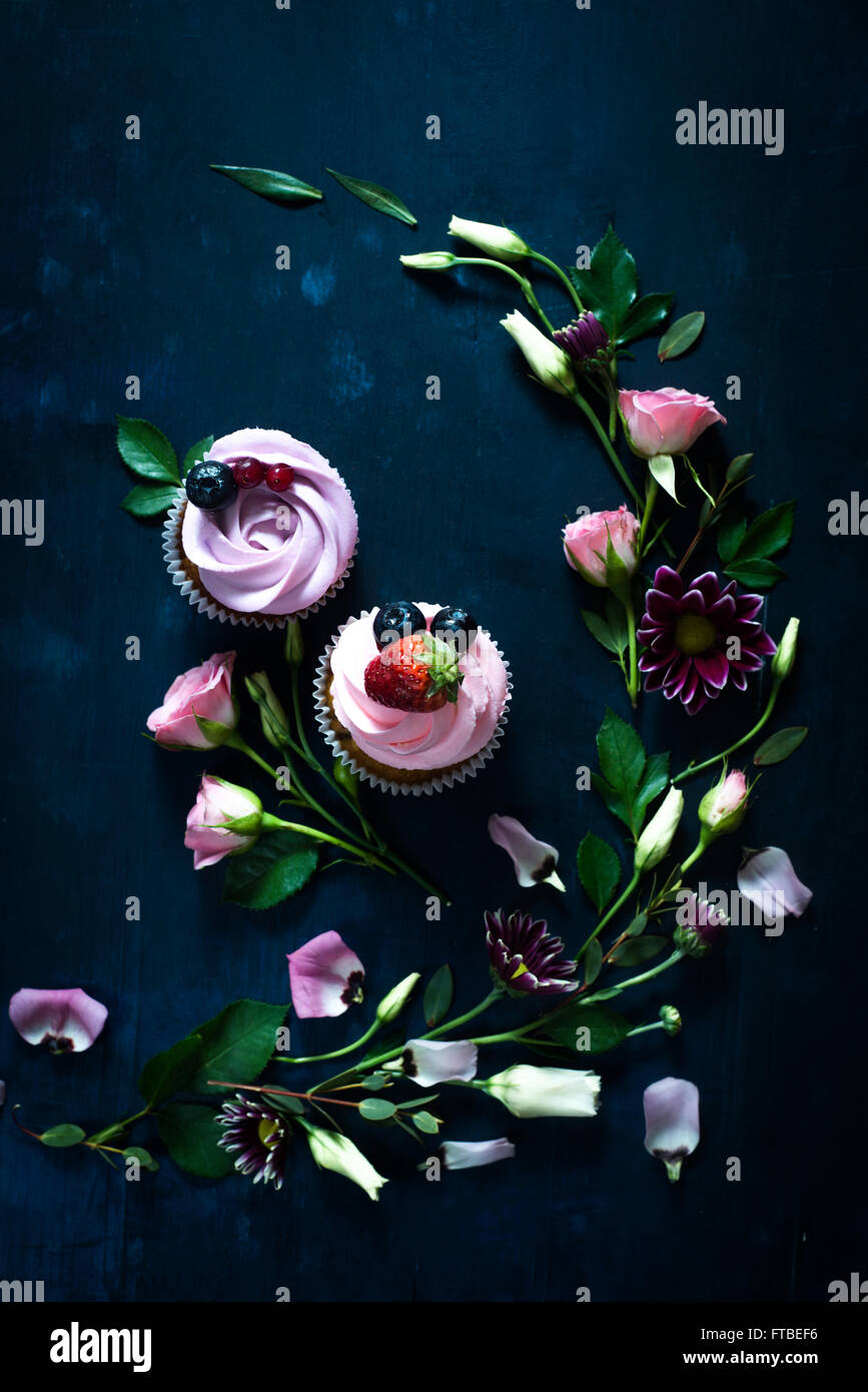 Sweet cupcakes on dark wooden background - Stock Image