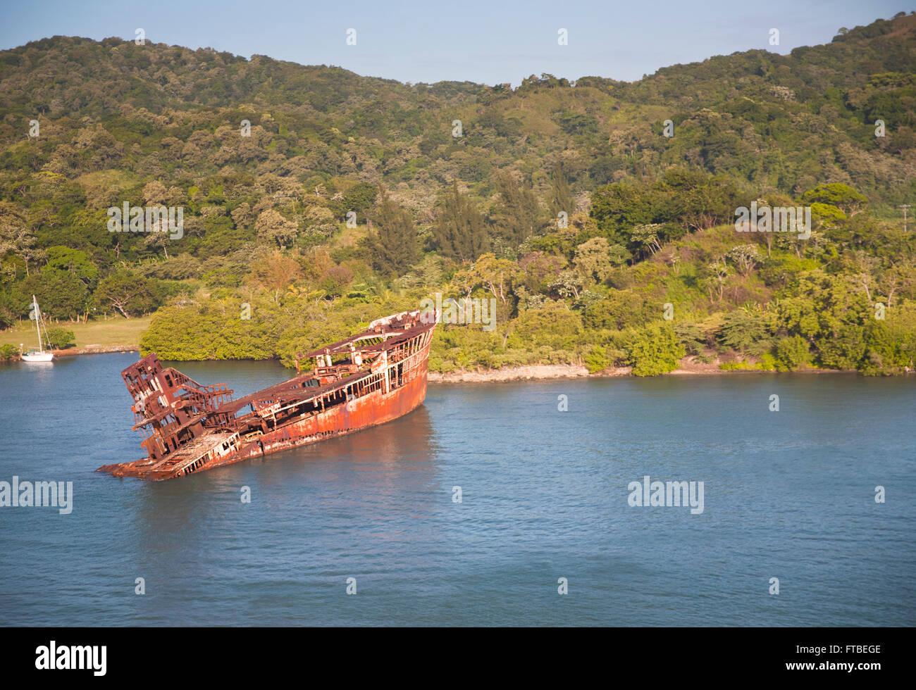 Sunken ship sitting in Mahogany Bar in Roatán, Honduras with the islands lush vegetation covering the hills - Stock Image