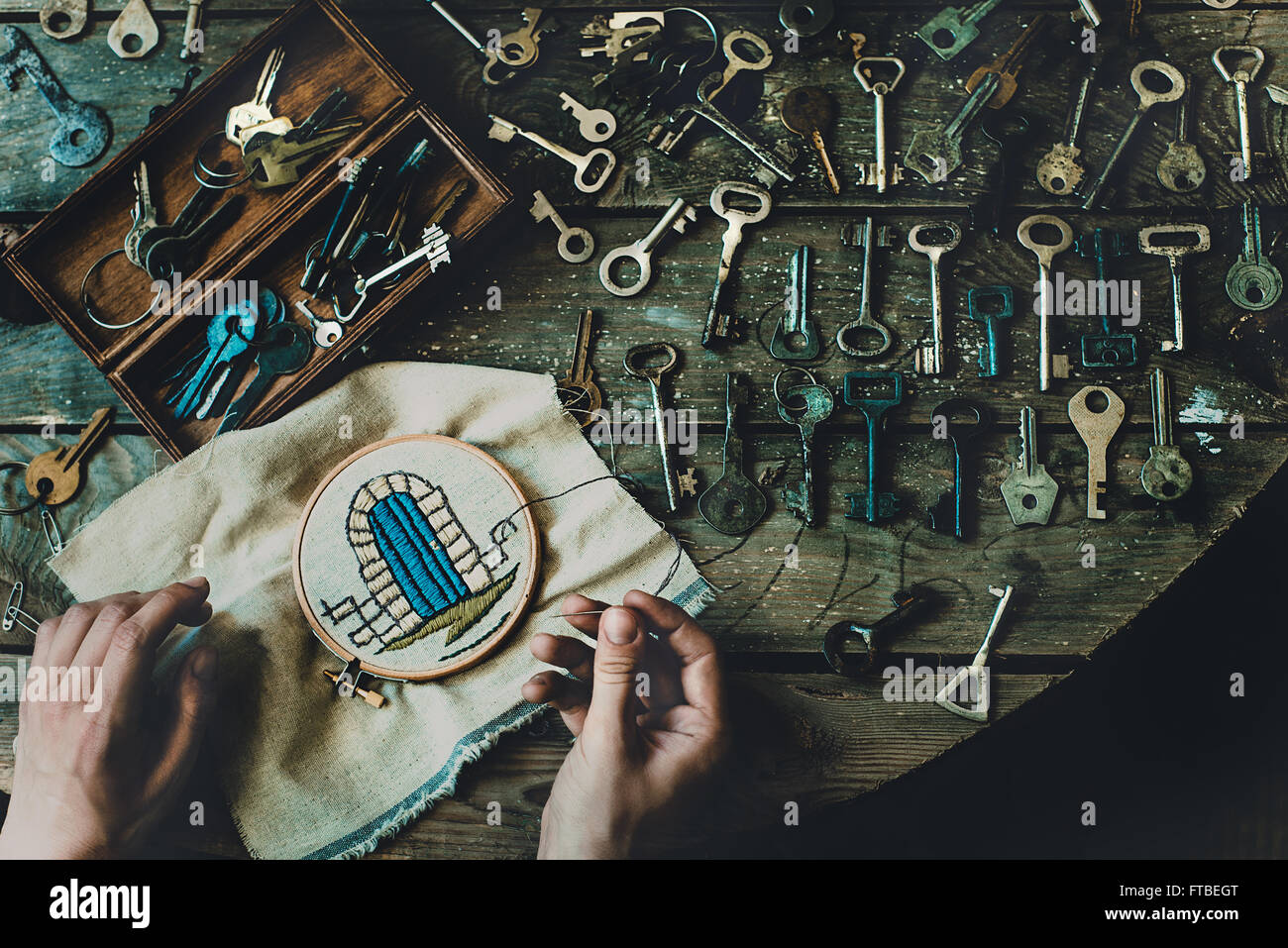 Wes Anderson from above top view hands keys embroidery needlework locked princess in the tower needle open texture - Stock Image