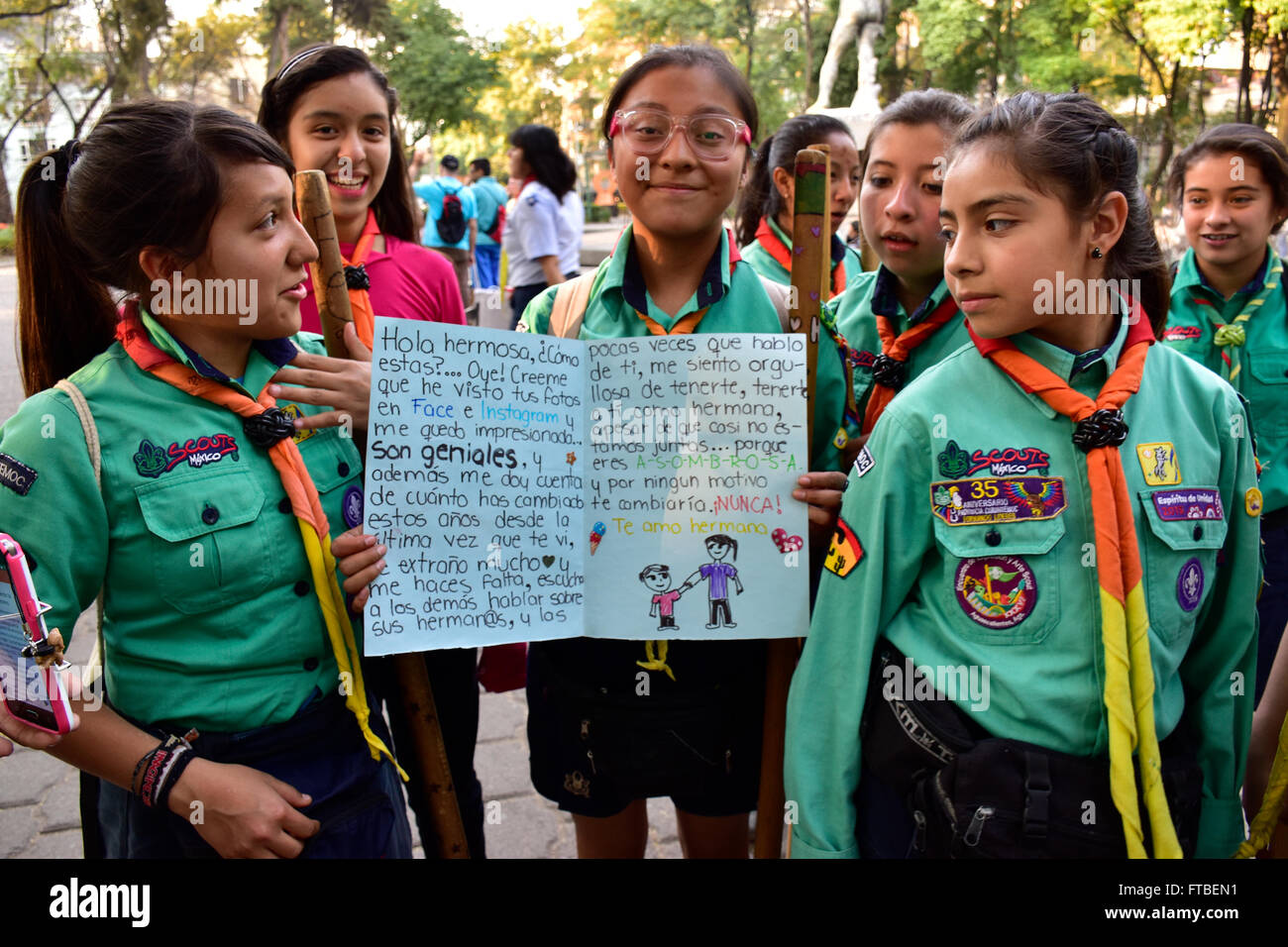 Girls Scouts holding a written card to an older Girl Scout. - Stock Image