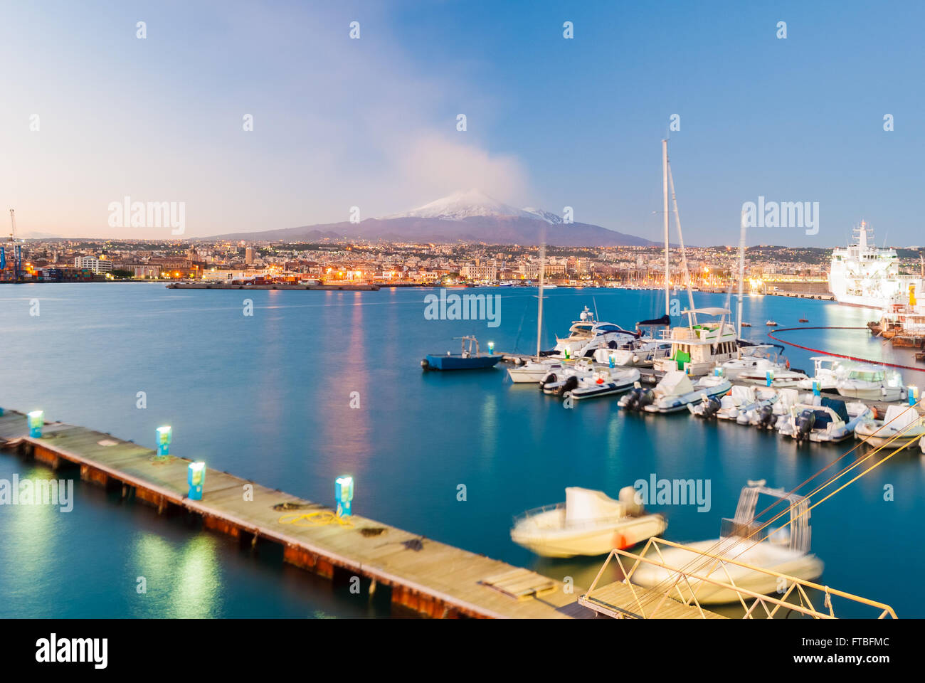 Skyline of Catania and its harbor with snowy volcano Etna in background after the sunset - Stock Image