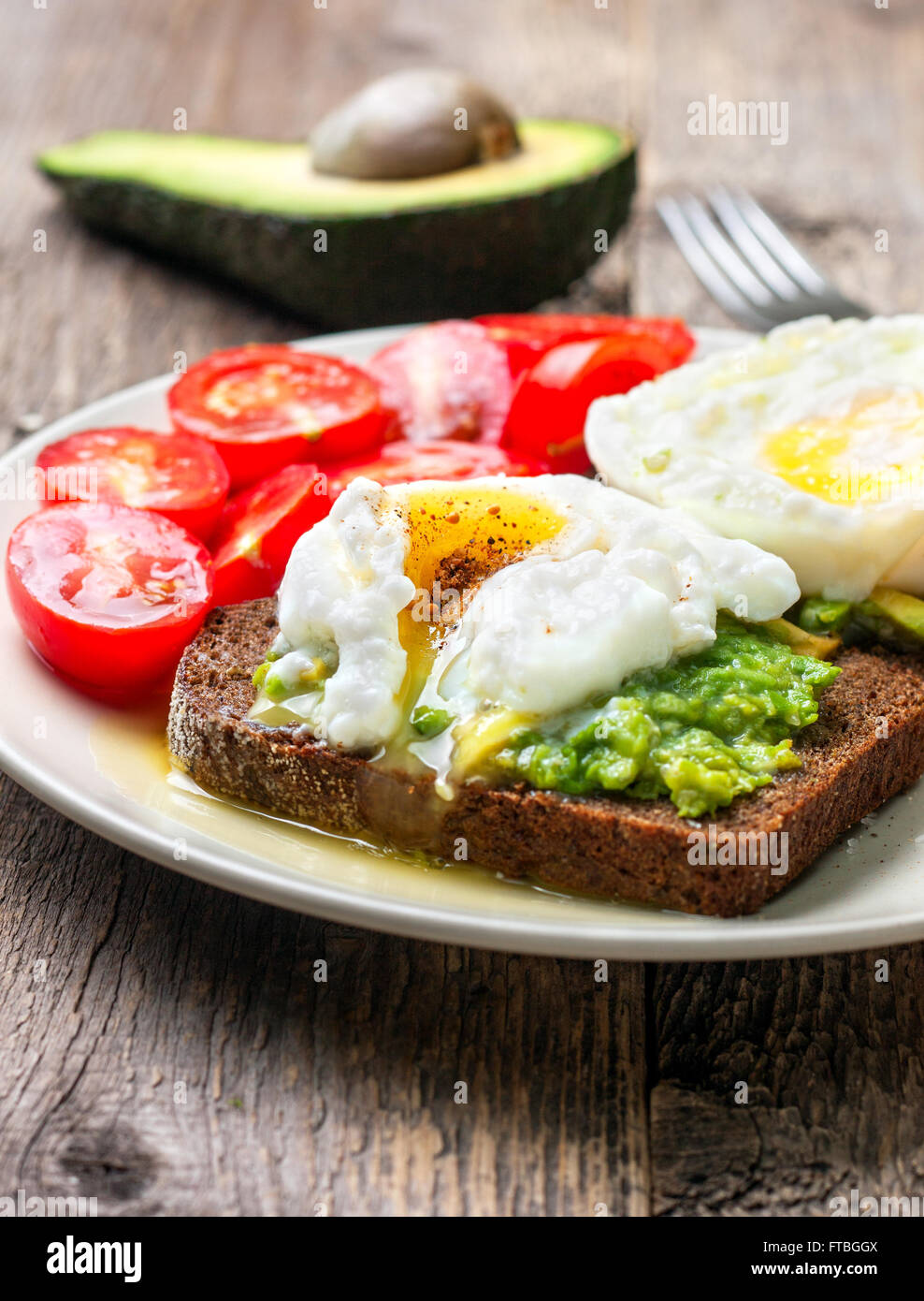 Open toast with avocado and egg, cherry tomatoes on a wooden background - Stock Image