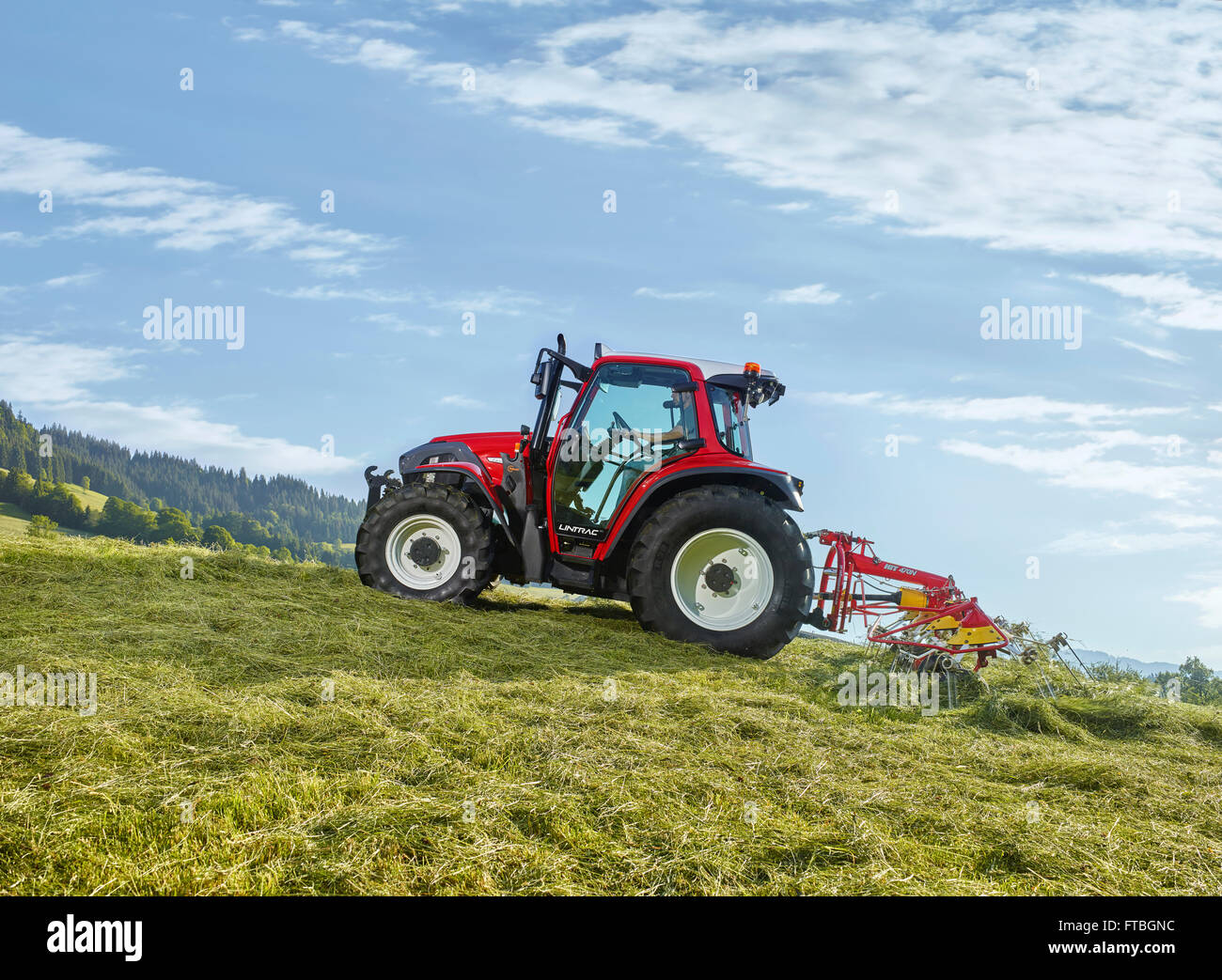 Tractor tedding the freshly cut hay with a tedder, Hopfgarten, Brixental, Tyrol, Austria - Stock Image