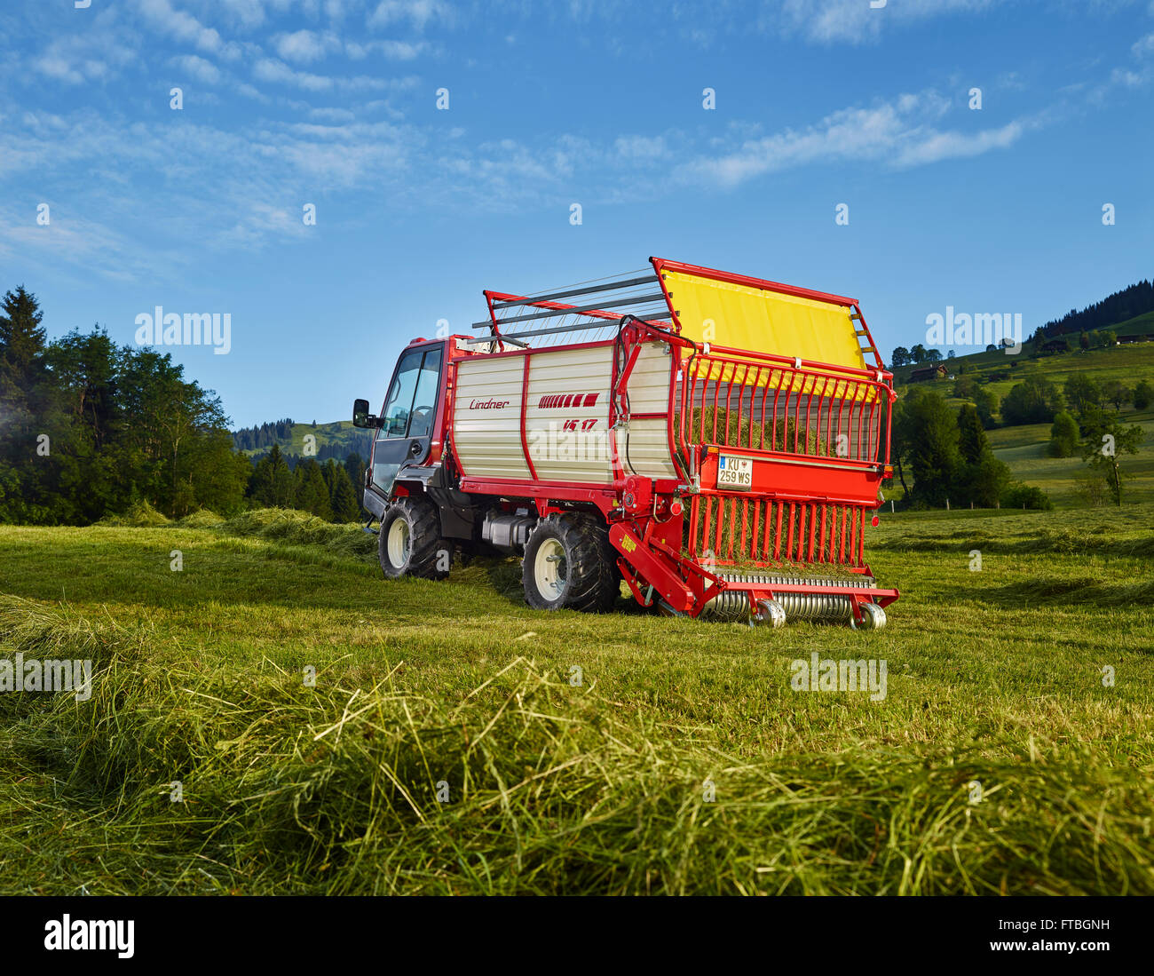 Unitrac transporter with forage trailer collecting the dried hay, Hopfgarten, Brixental, Tyrol, Austria - Stock Image