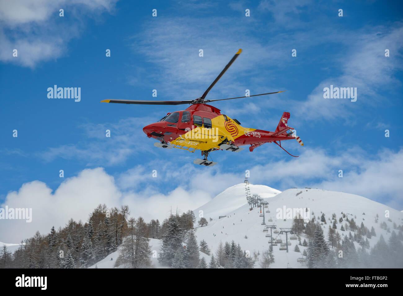 Helicopter in front of Mount Tscheyeck, Nauders ski resort in winter, Nauders, Tyrol, Austria - Stock Image