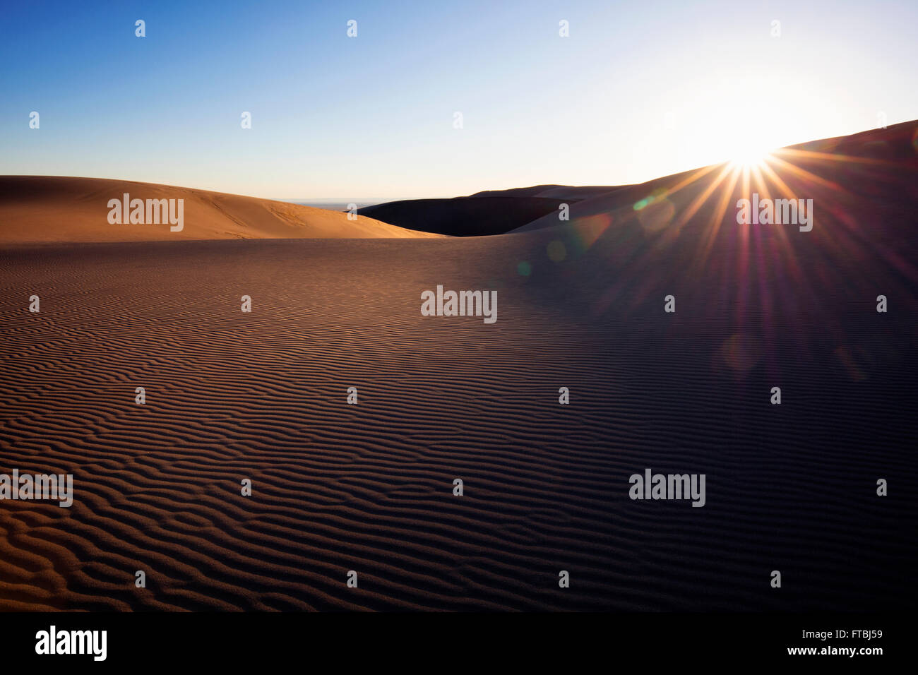 Sunlight peaking over sand dune in remote desert.  Great Sand Dunes National Park, Colorado, USA. Stock Photo