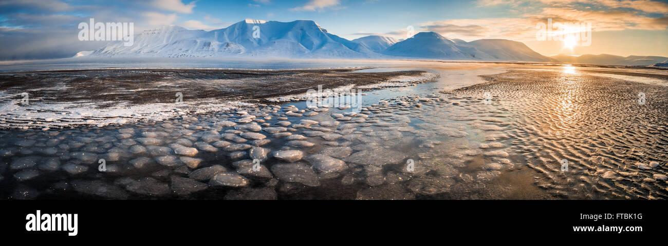 Sunrise ice formations on Sjøskrenten beach with views to Hiorthfjellet, Longyearbyen, Spitsbergen, Svalbard. - Stock Image