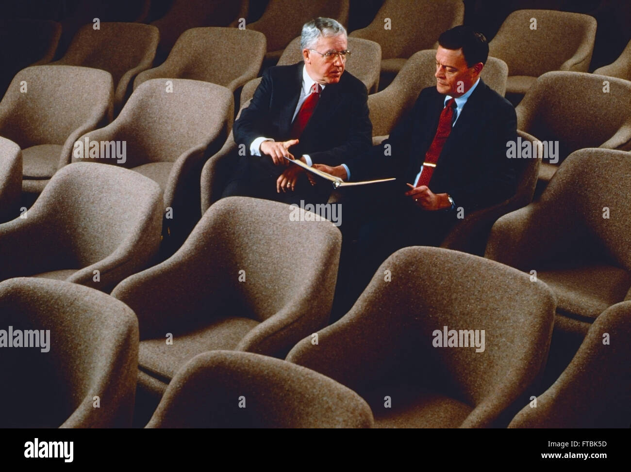 Two corporate business leaders seated in large conference room - Stock Image