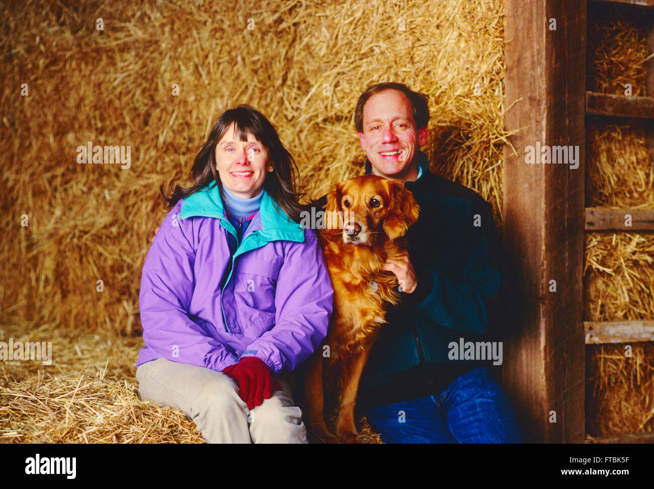 Environmental portrait in a barn of Photographer H. Mark Weidman; writer Marjorie Ackermann; and their Golden Retriever; - Stock Image