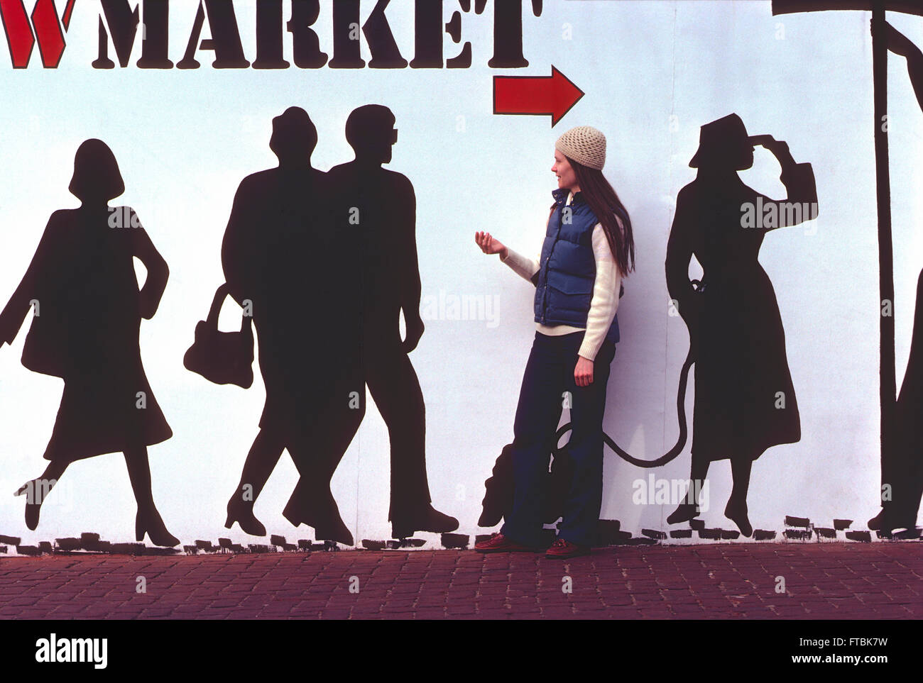 Attractive woman juxtaposed against life sized human figures in wall mural - Stock Image