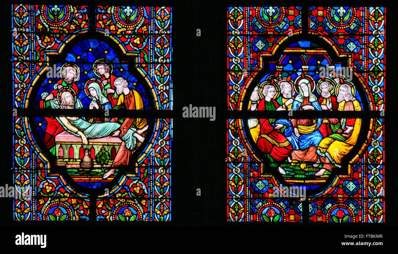 Stained glass window depicting Jesus laid in His tomb and Mother Mary and the Apostles at Pentecost - Stock Image