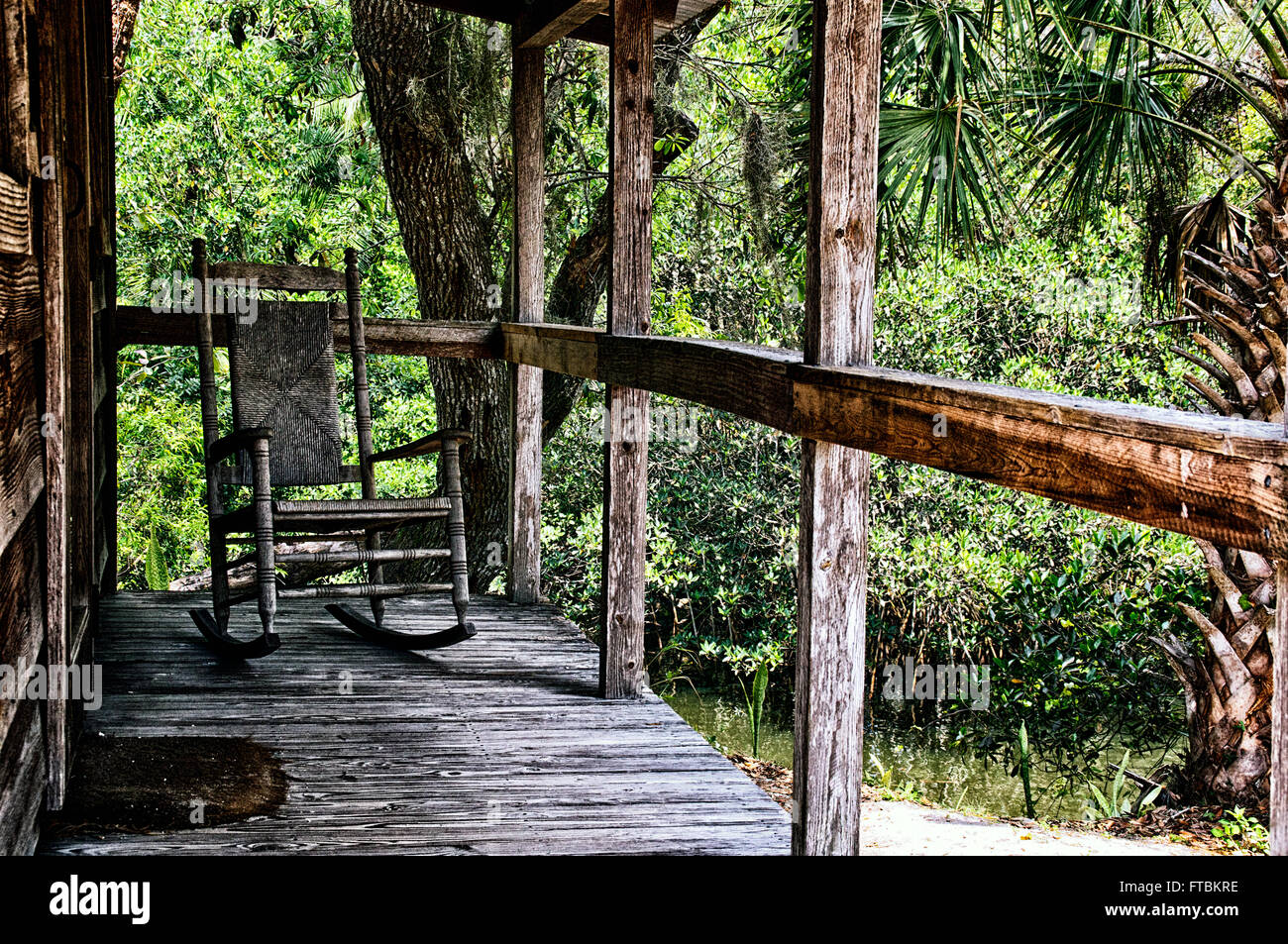 Looking across old wooden porch towards an empty rocking chair with wicker back in tropical estero florida setting. Koreshan State park & Looking across old wooden porch towards an empty rocking chair with ...