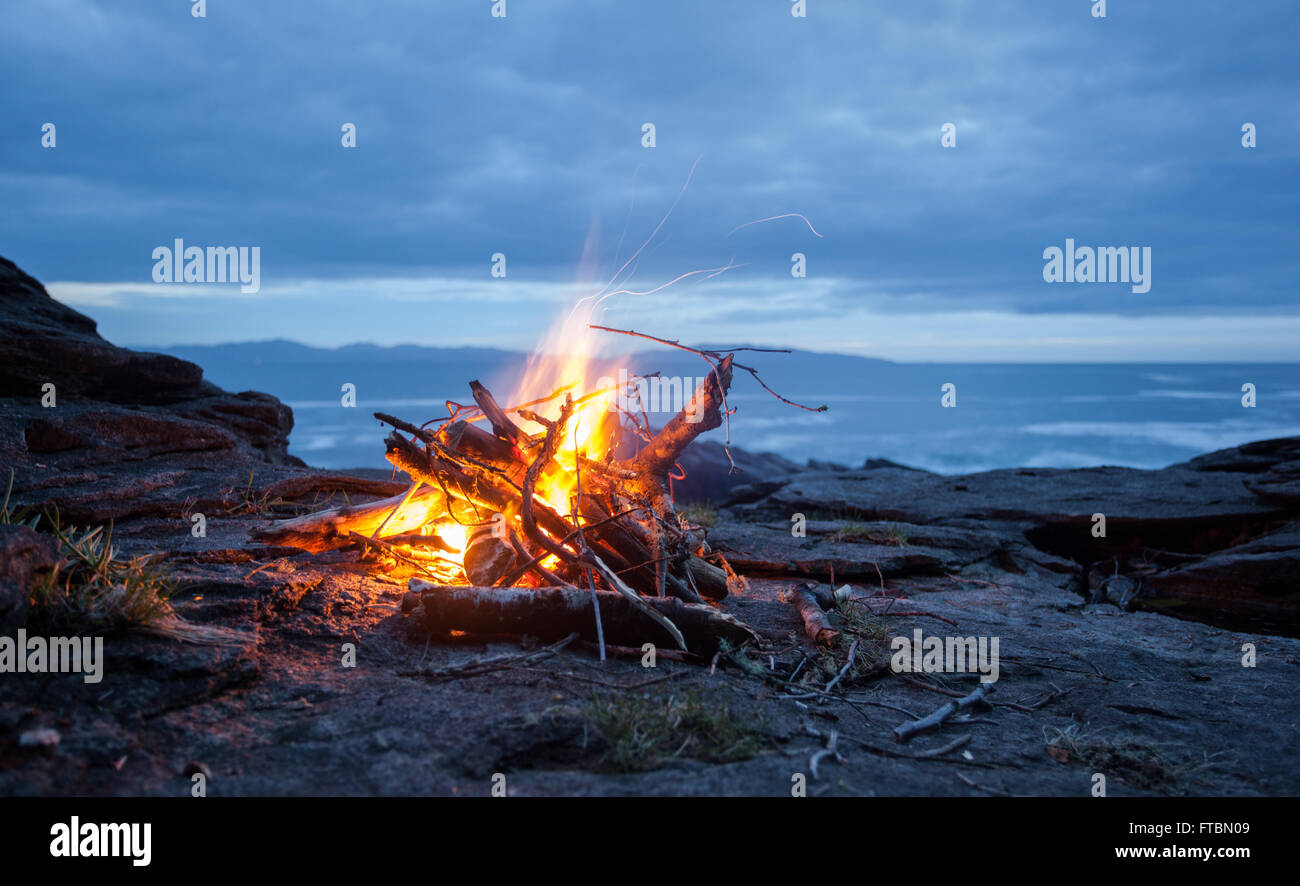 Beach Fire at Sunset, Juan de Fuca Strait, Vancouver Island, British Columbia - Stock Image