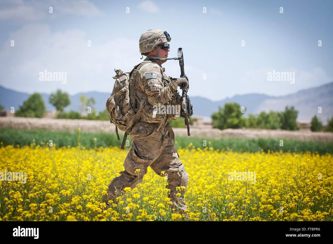 A U.S. Army paratrooper with the 82nd Airborne Division walks through a field of flowers while on patrol May 19, - Stock Image
