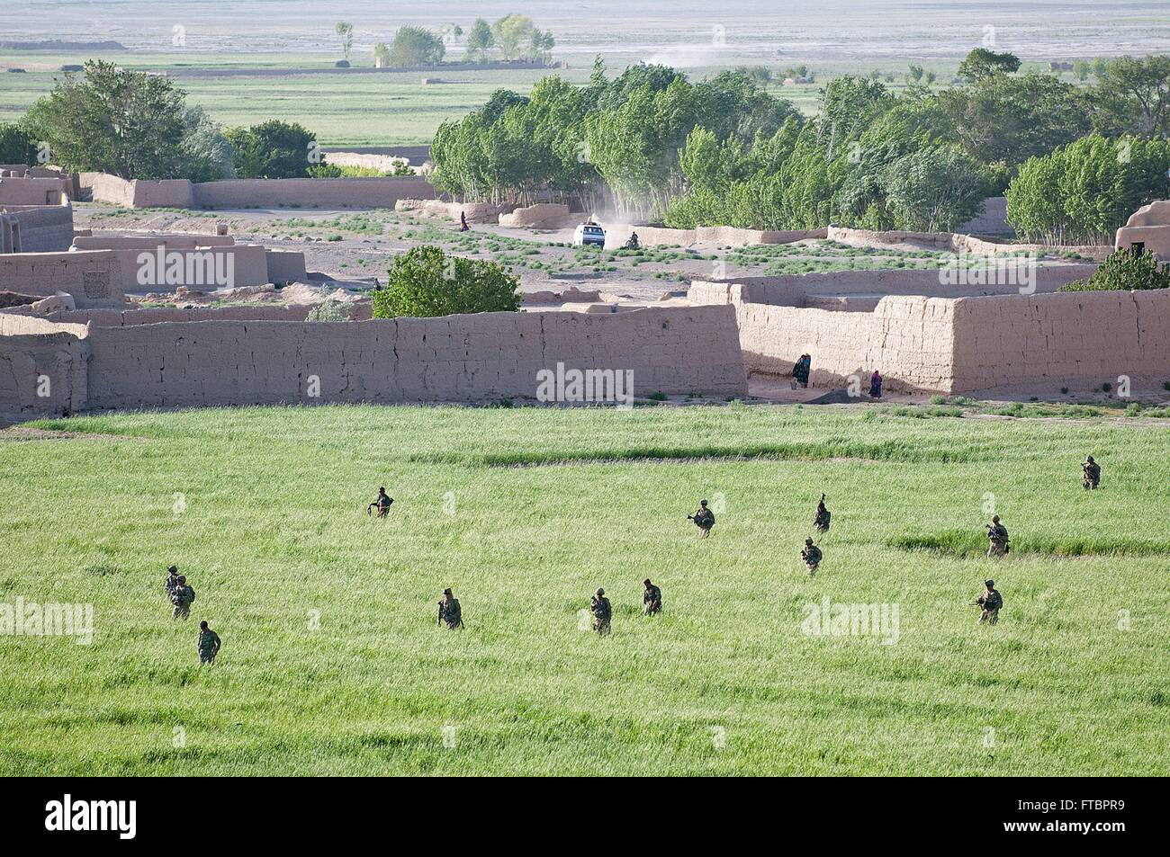U.S. Army paratroopers with the 73rd Cavalry Regiment cross an open farm field with Afghan soldiers during a patrol - Stock Image