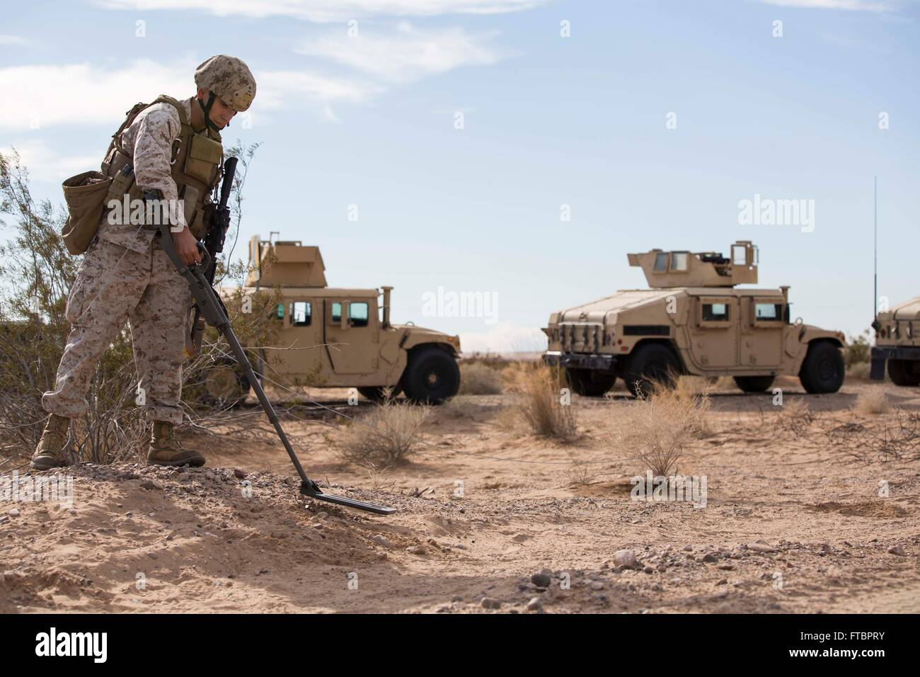 A U.S. Marine combat engineer sweeps for improvised explosive devices during a security force exercise in support - Stock Image