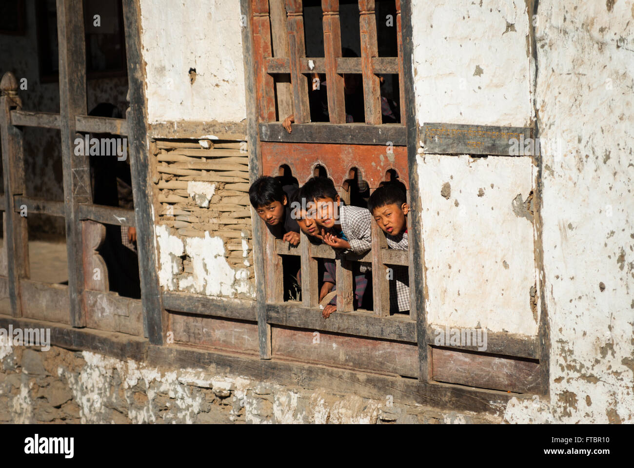 Children poke their heads out of a carved wooden window frame in their dilapidated school building in Nimshong village, - Stock Image