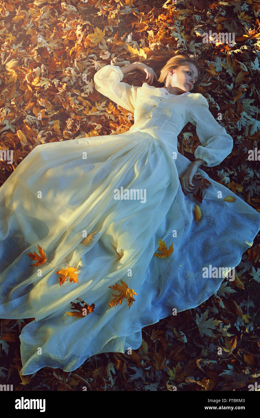 Beautiful woman with victorian dress on a bed of leaves. Sadness and loneliness concept Stock Photo