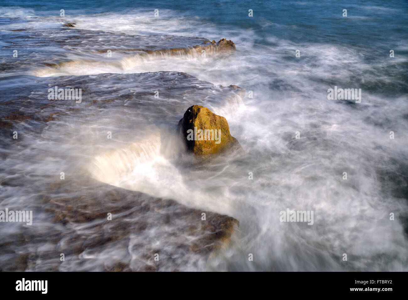 a rock in swirly water - Stock Image