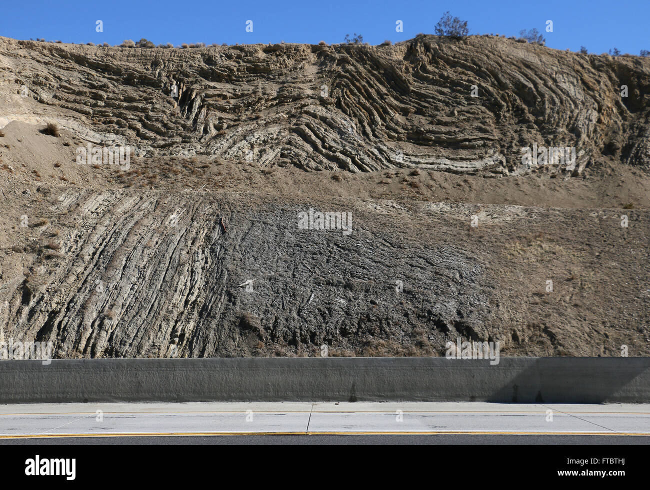 Deformed rock layers in road cut along San Andres fault County of Los Angeles - Stock Image