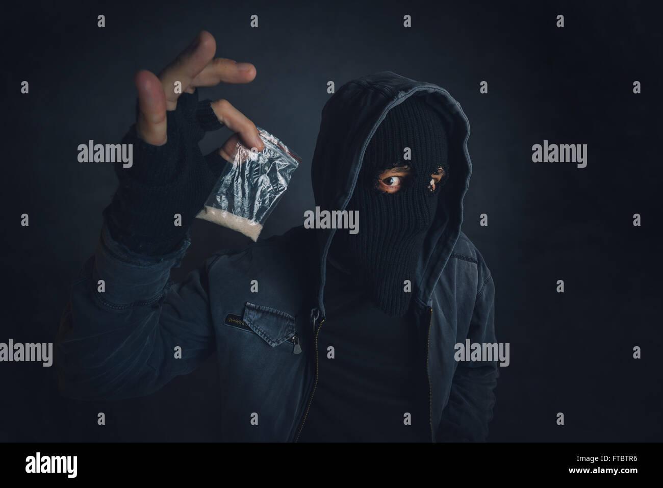 Drug dealer offering narcotic substance to addict on the street, unrecognizable hooded criminal selling drugs in - Stock Image