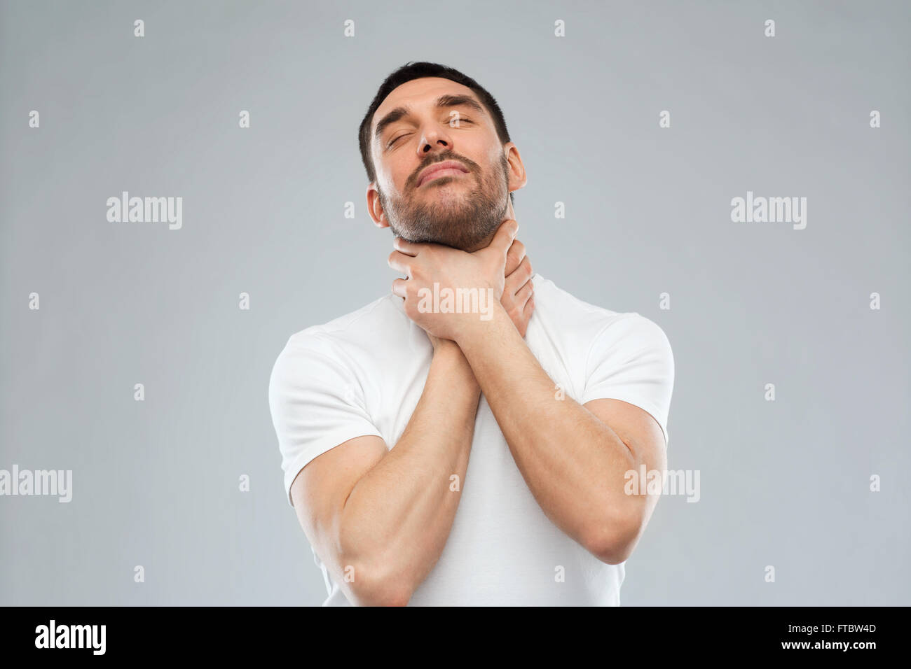 young man choking himself over gray background - Stock Image