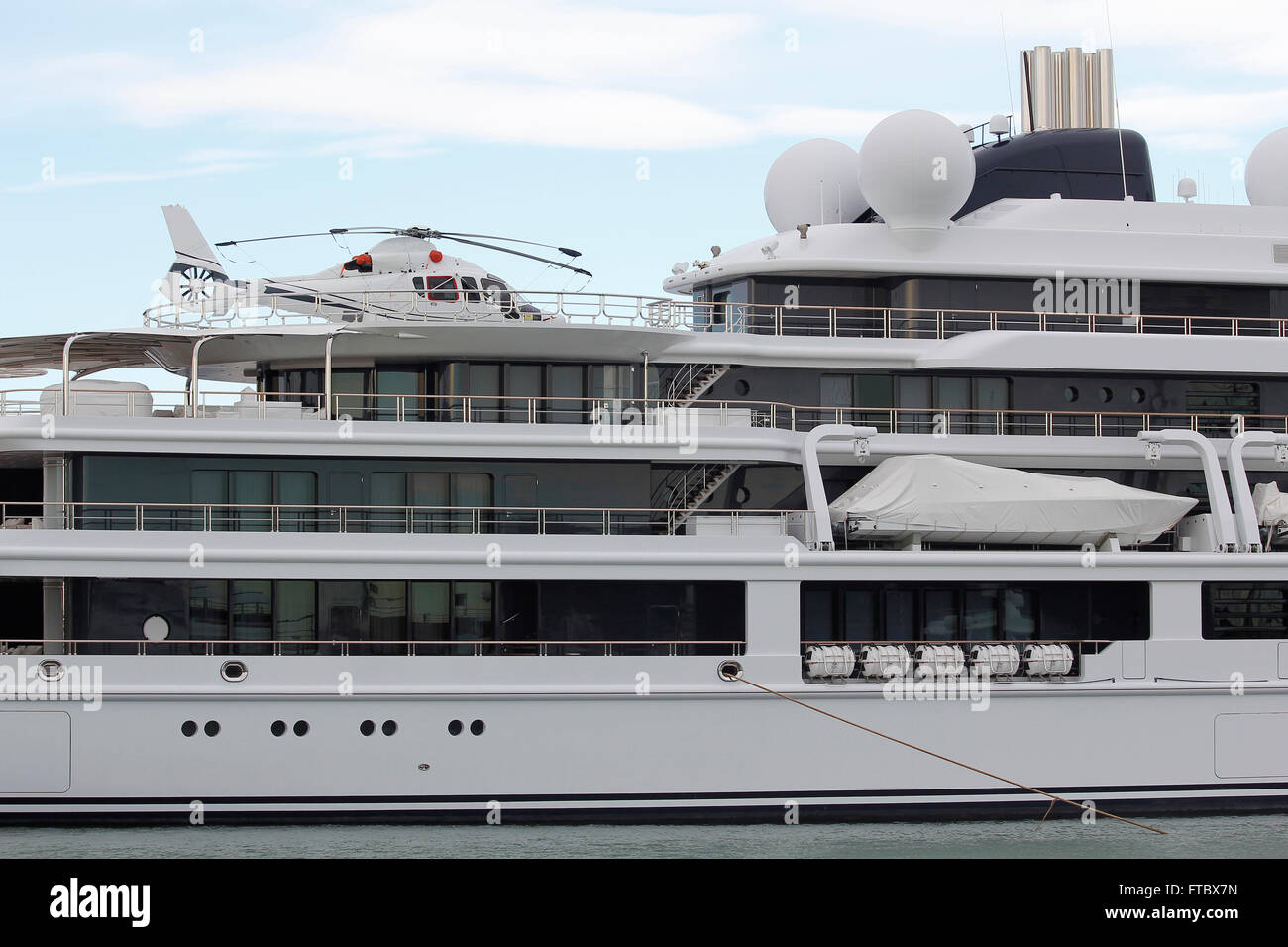Luxury yacht with helicopter, moored on harbor - Stock Image