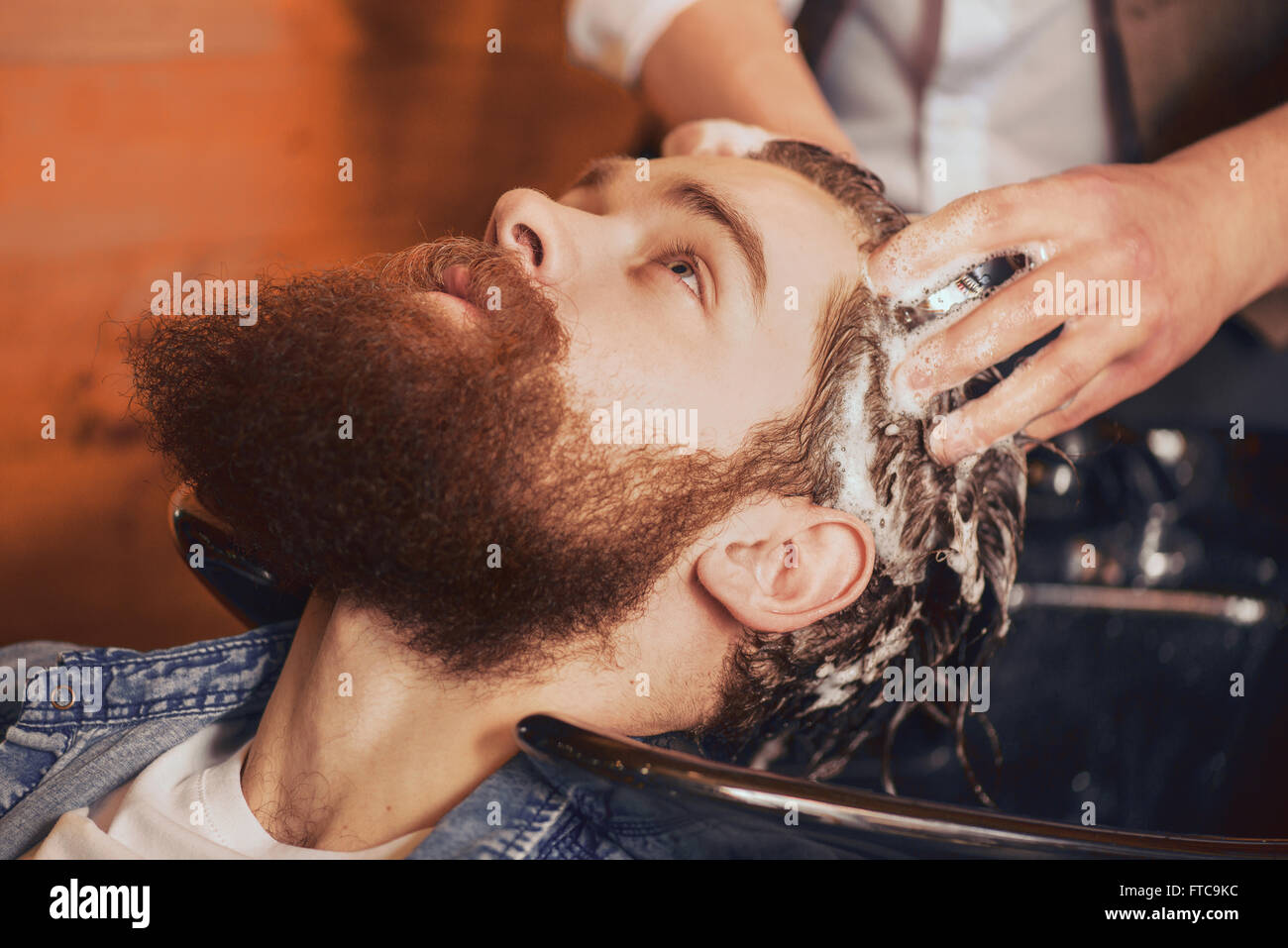 professional barber washing head of his client - Stock Image