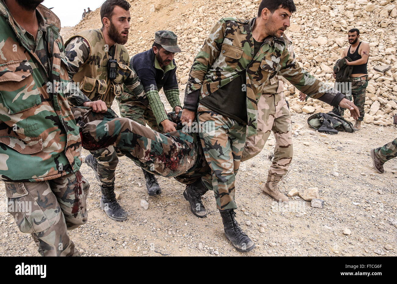 Palmyria, Syria. 26th Mar, 2016. Syrian government army soldiers carry their fellow soldier who was injured in an - Stock Image