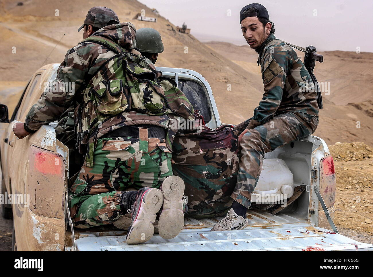Palmyria, Syria. 26th Mar, 2016. Syrian government army soldiers tending to their fellow soldier who was injured - Stock Image