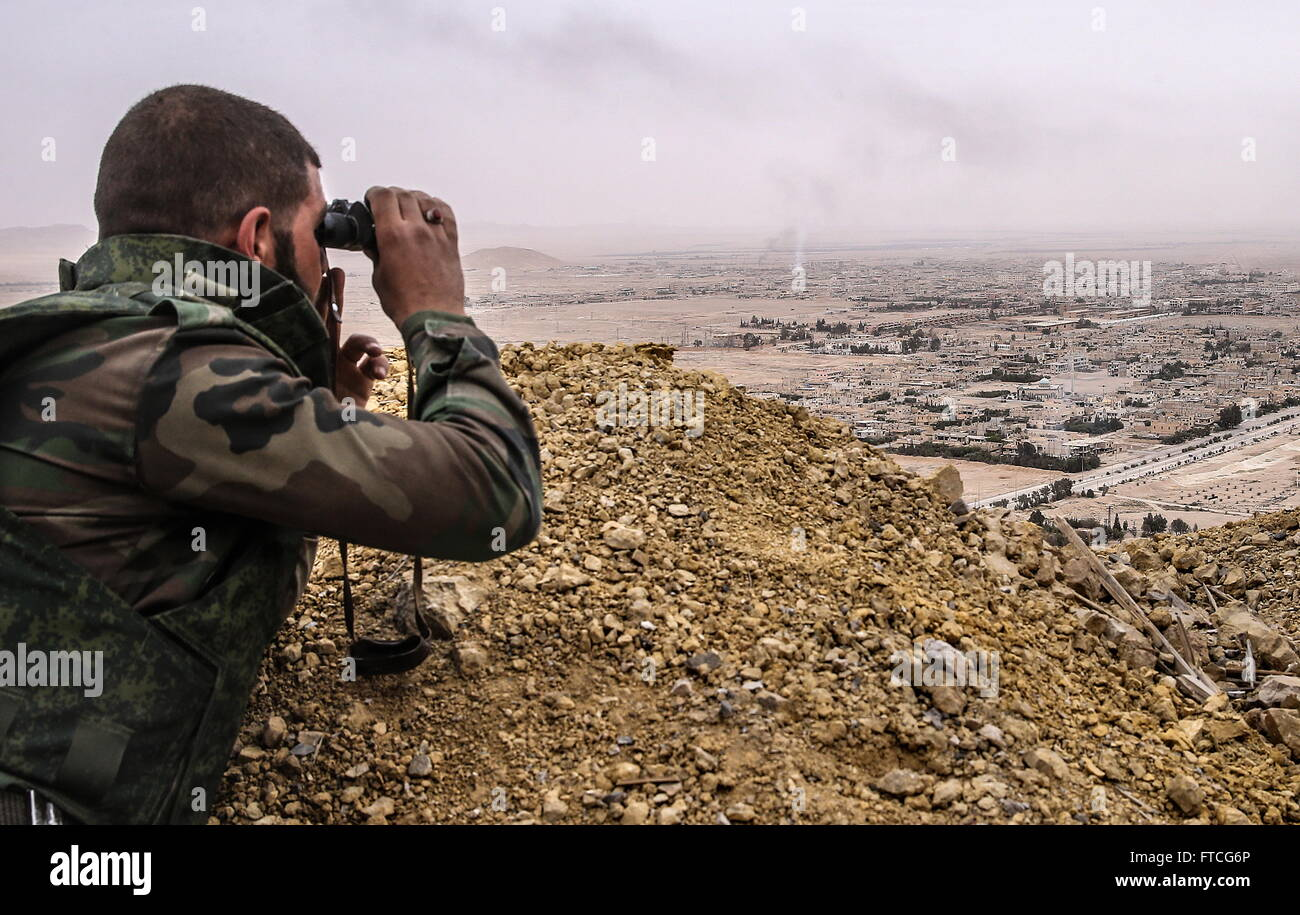 Palmyria, Syria. 26th Mar, 2016. A Syrian government army soldier looks through binoculars at Palmyra from the top - Stock Image