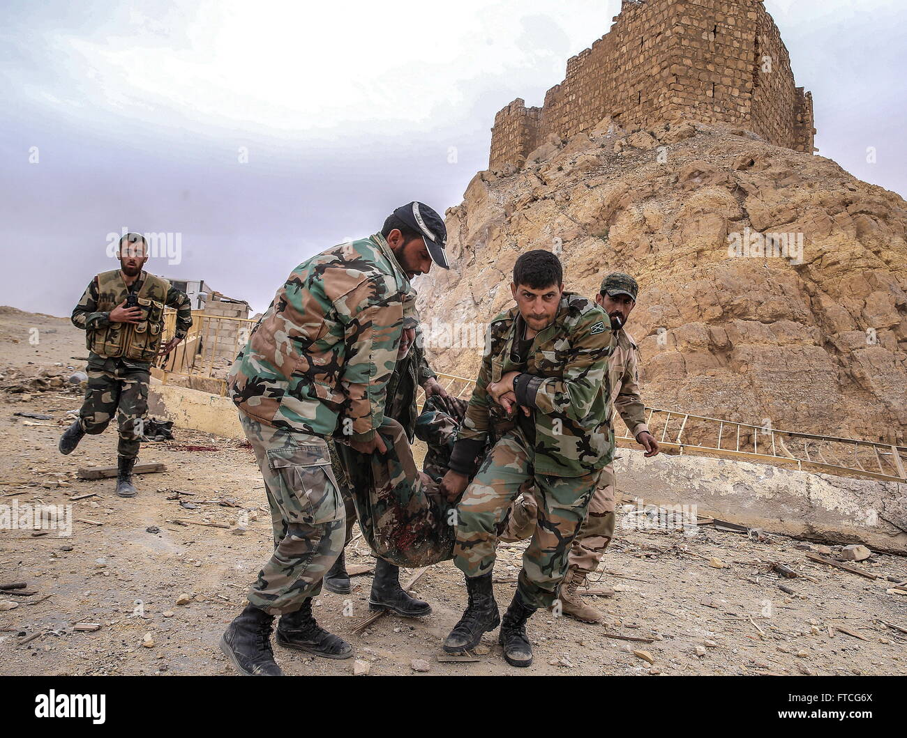 Palmyria, Syria. 26th Mar, 2016. Syrian government army soldiers tending to their fellow soldier who was injured Stock Photo