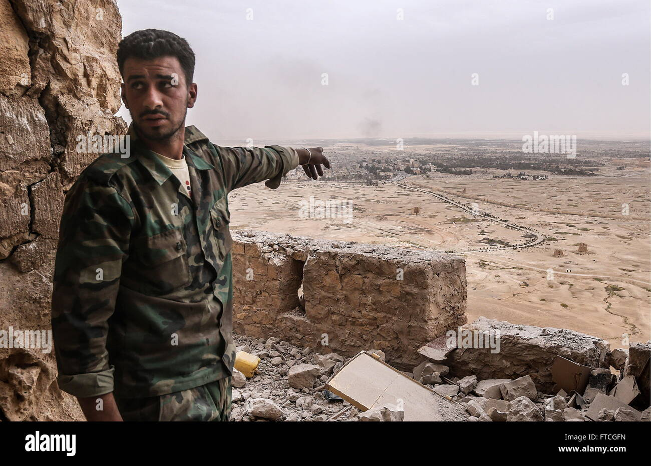 Palmyria, Syria. 26th Mar, 2016. A Syrian government army soldier points to Palmyra from the top of Fakhr al-Din - Stock Image