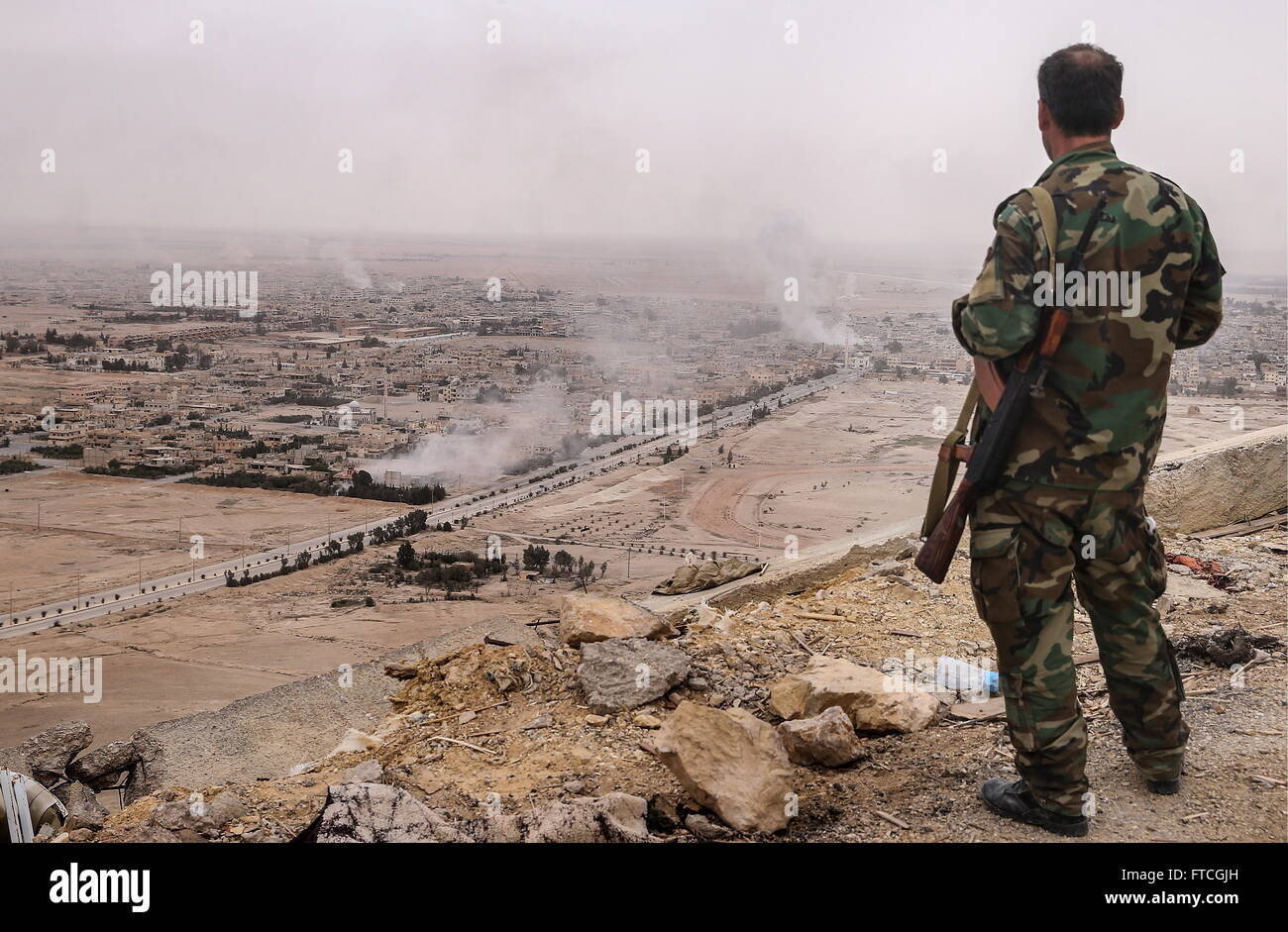 Palmyria, Syria. 26th Mar, 2016. A Syrian government army soldier looks at Palmyra from the top of Fakhr al-Din - Stock Image