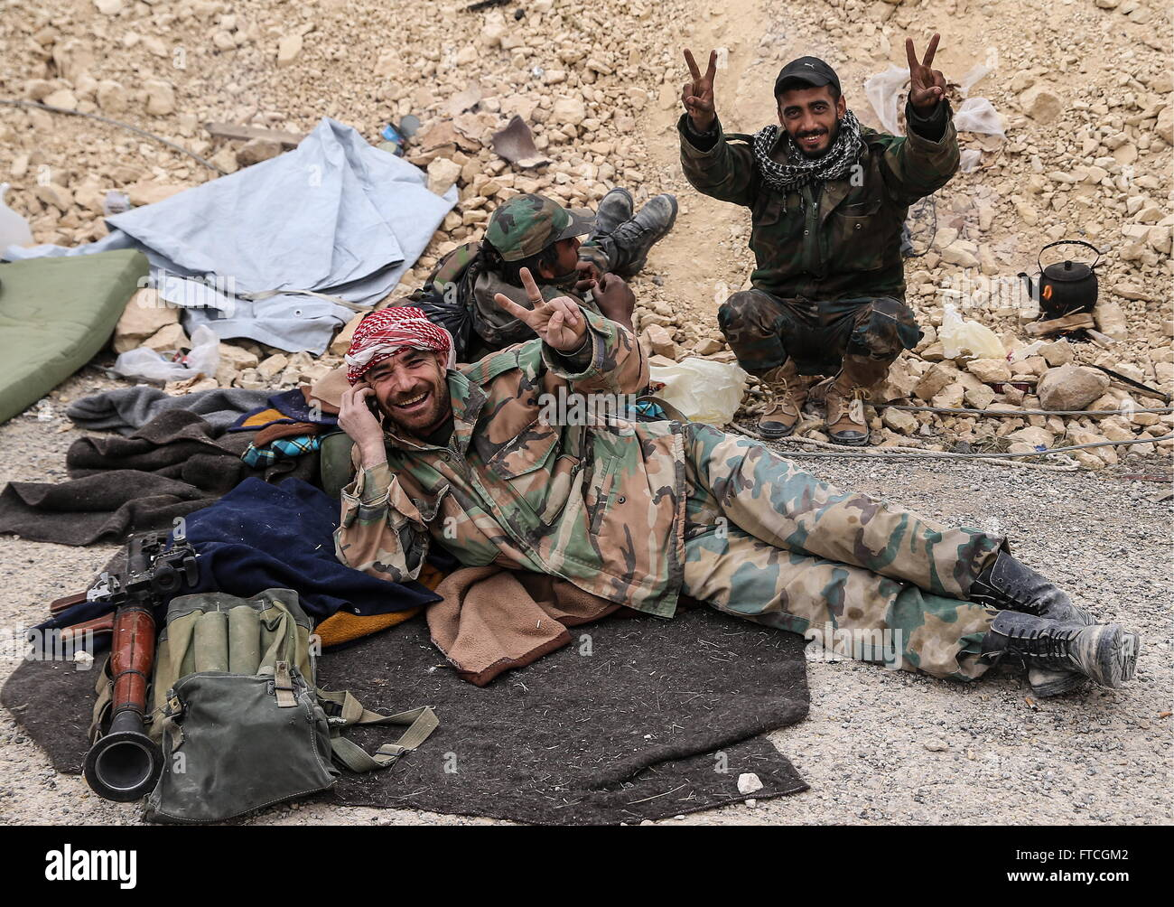 Palmyria, Syria. 26th Mar, 2016. Syrian government army soldiers show the V sign at the camera as they take reast - Stock Image