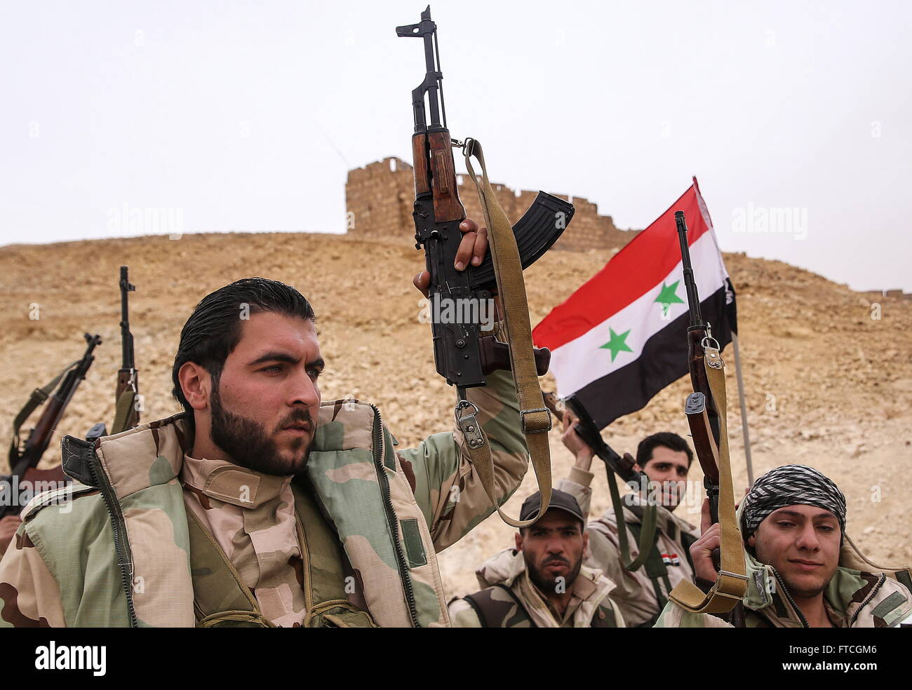 Palmyria, Syria. 26th Mar, 2016. Syrian government army soldiers with a Syrian national flag near Fakhr al-Din al - Stock Image