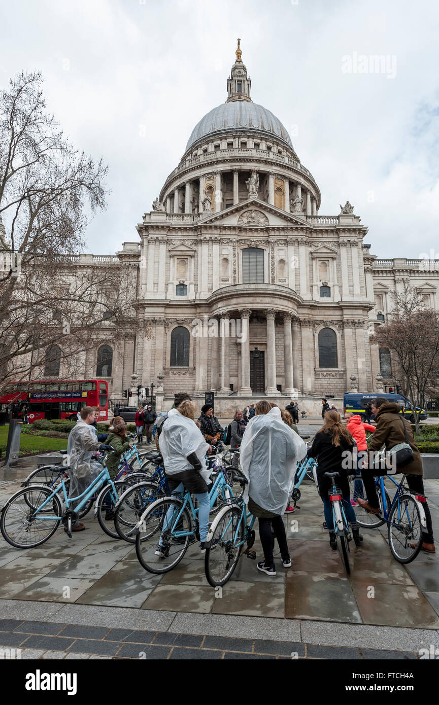 London, UK. 27th March 2016. UK Weather: Tourists on a cycle tour wear rain ponchos outside St. Paul's on Easter - Stock Image