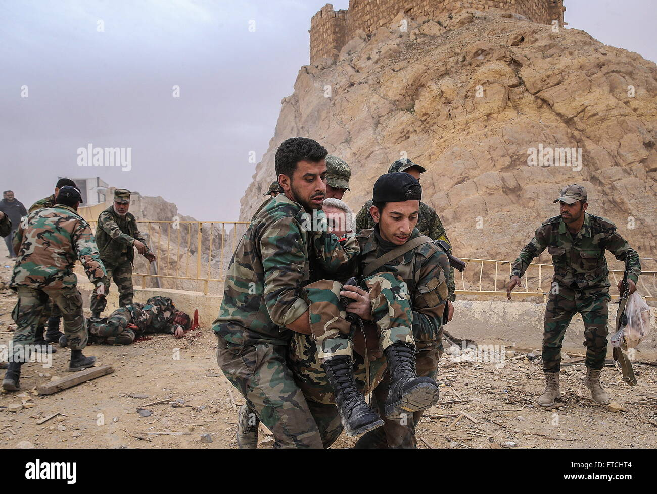 Palmyria, Syria. 26th Mar, 2016. Soldiers of the Syrian government army help their fellow soldier after an explosion Stock Photo