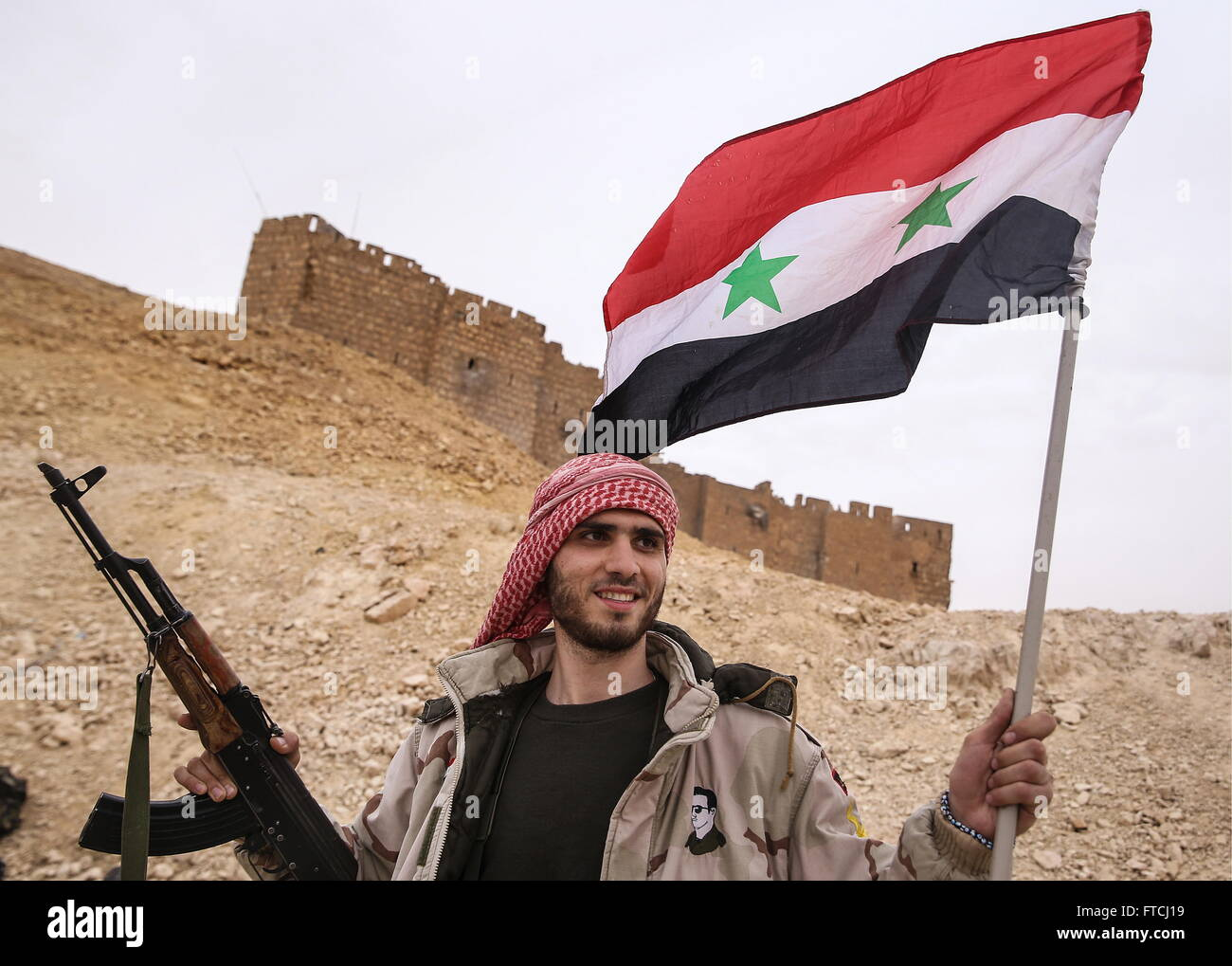 Palmyria, Syria. 26th Mar, 2016. A soldier of the Syrian government army with a Syrian national flag near Fakhr - Stock Image