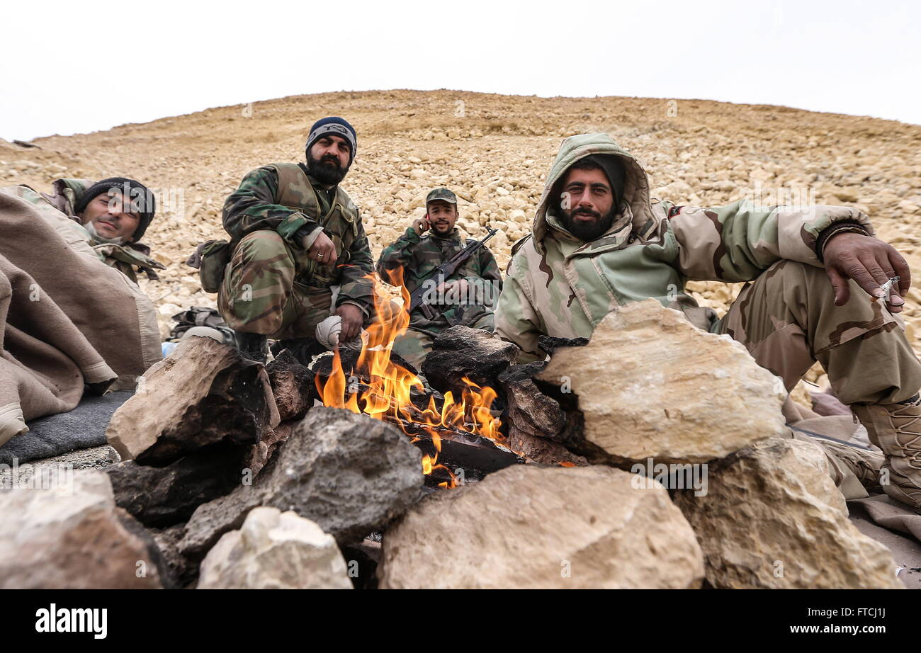 Palmyria, Syria. 26th Mar, 2016. Soldier of the Syrian government army warm themselves by a fire near Fakhr al-Din - Stock Image