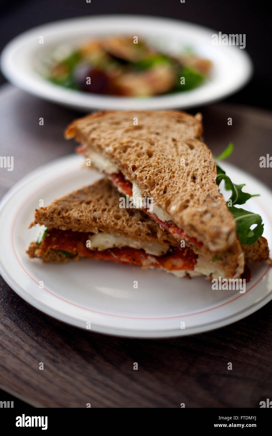 Italian salami and sheep cheese sandwich with brown bread. - Stock Image