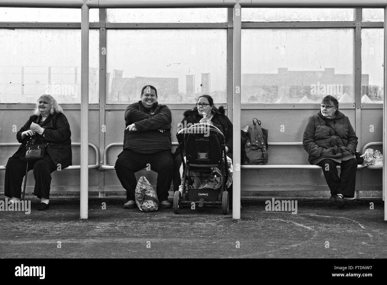 A candid image of four overweight people sitting in a beach shelter at Skegness, Lincolnshire, UK - Stock Image