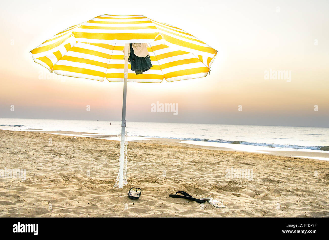 yellow umbrella lonely on the beach at sunset in Puglia - Stock Image
