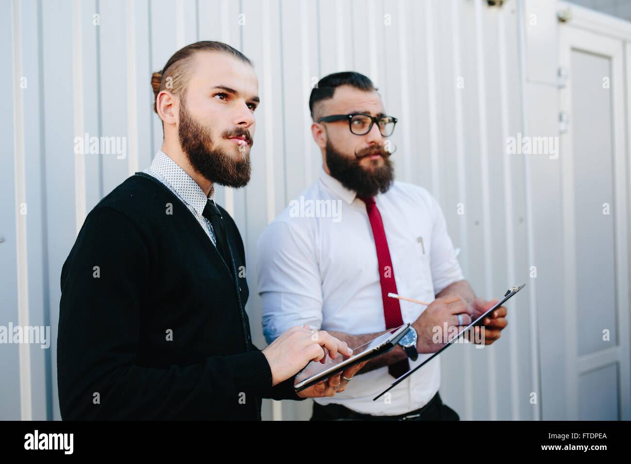Two bearded businessman looking at something - Stock Image